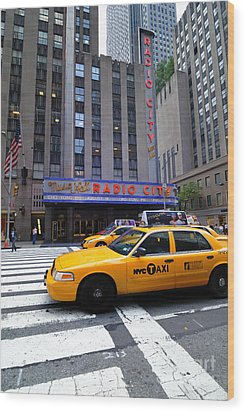 Yellow Cabs Pass In Front Of Radio City Music Hall Wood Print by Amy Cicconi