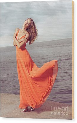 Young Woman In Orange Dress Flying In The Wind At Sea Shore Wood Print by Oleksiy Maksymenko