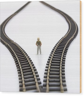 Figurine Between Two Tracks Leading Into Different Directions  Symbolic Image For Making Decisions. Wood Print by Bernard Jaubert