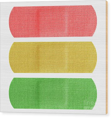 Red Yellow And Green Bandaids Wood Print by Blink Images