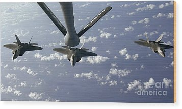 A Three Ship Formation Of F-22 Raptors Wood Print by Stocktrek Images
