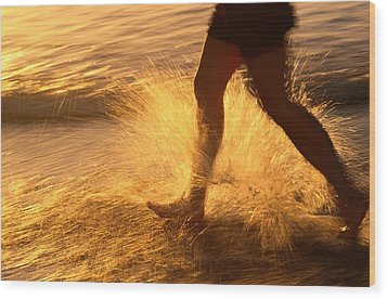 A Runner Splashing Through The Surf Wood Print by Phil Schermeister
