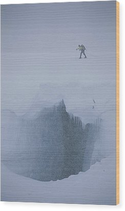 A Skier Above A Deep Glacier Crevasse Wood Print by John Burcham