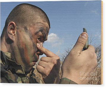 A Soldier Applying Face Paint Prior Wood Print by Stocktrek Images