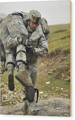 A Soldier Transports A Fellow Wounded Wood Print by Stocktrek Images
