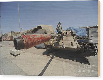 A T-55 Tank With Two Children Playing Wood Print by Andrew Chittock