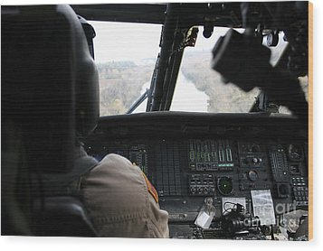 A Uh-60 Blackhawk Flies The River To An Wood Print by Terry Moore