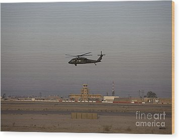 A Uh-60 Blackhawk Helicopter Flies Wood Print by Terry Moore