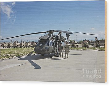 A Uh-60l Blackhawk Parked On Its Pad Wood Print by Terry Moore
