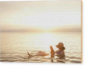 A Woman Reads A Book While Floating Wood Print by Taylor S. Kennedy