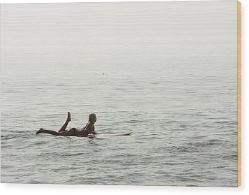 A Woman Rests On Her Surfboard Waiting Wood Print by Tim Davis