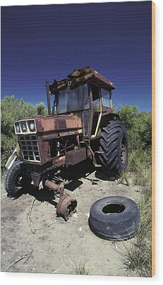 An Abandoned Tractor Rusts Away Wood Print by Jason Edwards