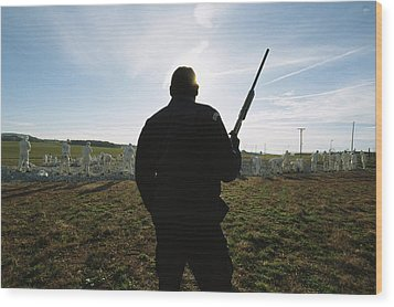 An Armed Guard Watches Over Inmates Wood Print by Bill Curtsinger