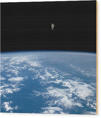 An Astronaut Propelled Above The Earth Wood Print by Nasa