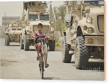 An Iraqi Boy Rides His Bike Past A U.s Wood Print by Stocktrek Images
