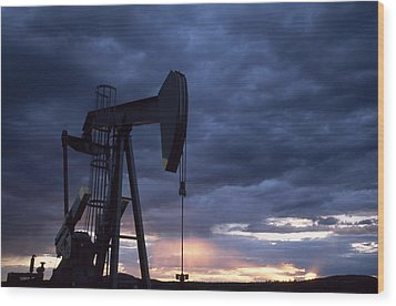 An Oil Rig Silhouetted At Sunset Wood Print by Joel Sartore