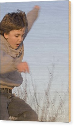 Boy Jumping Off Sand Dune Wood Print by Christopher Purcell