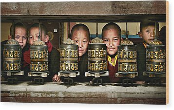 Buddhist Monks In Red Robes Look Out Of The Prayer Wheels With M Wood Print by Max Drukpa