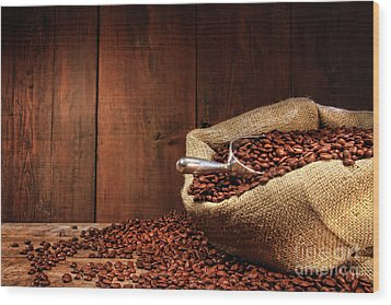 Burlap Sack Of Coffee Beans Against Dark Wood Wood Print by Sandra Cunningham