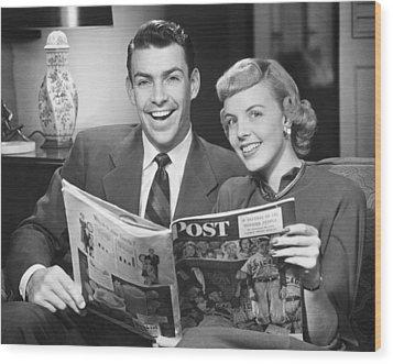 Couple Sitting On Sofa, Holding Magazine, (b&w), Portrait Wood Print by George Marks