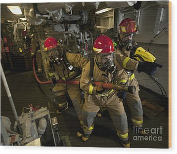 Firemen Combat A Simulated Fire Aboard Wood Print by Stocktrek Images
