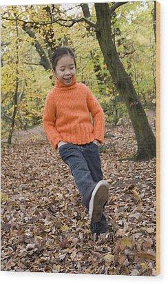 Girl Kicking Leaves Wood Print by Ian Boddy