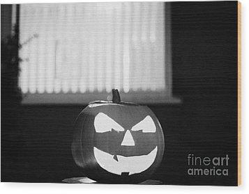Illuminated Halloween Pumpkin Jack-o-lantern Outside The Window Of A House To Ward Off Evil Spirits  Wood Print by Joe Fox