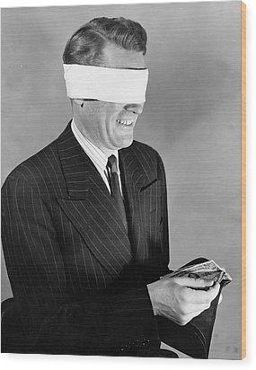 Man Wearing Blindfold Holding Money (b&w) Wood Print by Hulton Archive