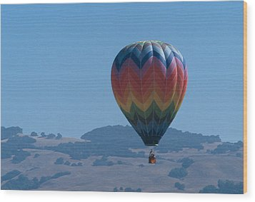 Rainbow Balloon Over Hills Wood Print by Bonnie Muir