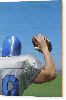 Rear View Of A Football Player Throwing A Football Wood Print by Stockbyte
