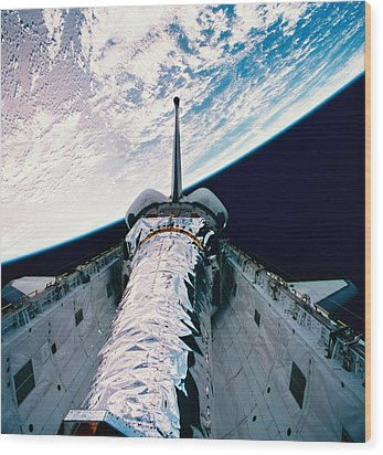 The Space Shuttle With Its Open Cargo Bay Orbiting Above The Earth Wood Print by Stockbyte