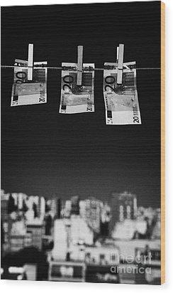 Three Twenty Euro Banknotes Hanging On A Washing Line With Blue Sky Over City Skyline Wood Print by Joe Fox