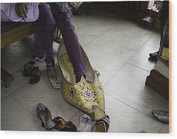 Trying On A Very Large Decorated Shoe Wood Print by Ashish Agarwal