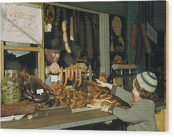 Vendor Holds Up Sausages For Young Girl Wood Print by Volkmar Wentzel