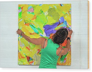 Woman Adjusting A Painting Wood Print by Sami Sarkis