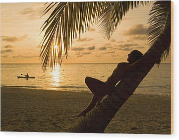 Woman Resting On A Palm Tree At Sunset Wood Print by Richard Nowitz