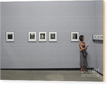 Woman Watching Photos At Exhibition Wood Print by Sami Sarkis