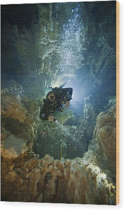 A Diver Ascends A Deep Shaft In Dans Wood Print by Wes C. Skiles