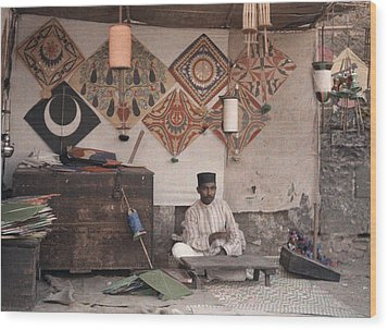 A Kite Merchant Sits In His Store Wood Print by Gervais Courtellemont