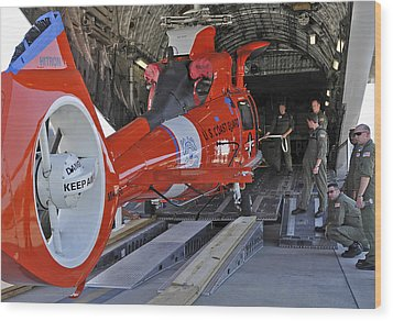 An Aircrew Loads A Coast Guard Hh-65 Wood Print by Stocktrek Images