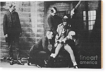 Criminal Being Held Down For Mug Shot Wood Print by Photo Researchers