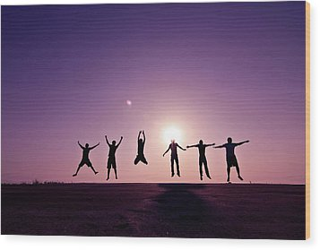 Friends Jumping Against Sunset Wood Print by Kazi Sudipto photography