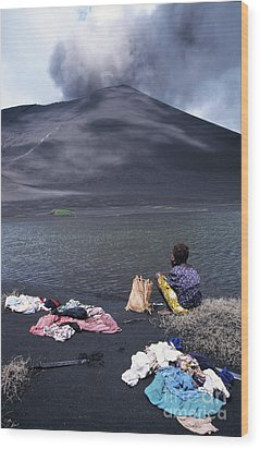 Girl Washing Clothes In A Lake With The Mount Yasur Volcano Emitting Smoke In The Background Wood Print by Sami Sarkis