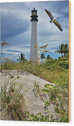 Pelican Flying Over Cape Florida Lighthouse Wood Print by Justin Kelefas