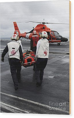 Personnel Carry An Injured Sailor Wood Print by Stocktrek Images