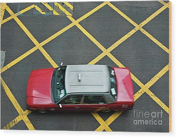 Red Taxi Cab Driving Over Yellow Lines In Hong Kong Wood Print by Sami Sarkis