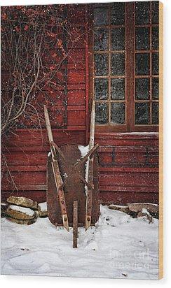 Rusty Wheelbarrow Leaning Against Barn In Winter Wood Print by Sandra Cunningham