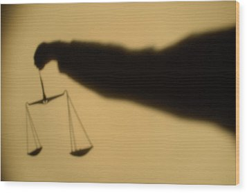 Shadow Of A Person's Arm Holding Out The Scales Of Justice Wood Print by Sami Sarkis