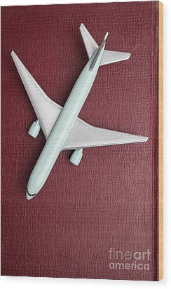 Wood Print featuring the photograph Toy Airplane Over Red Book Cover by Edward Fielding