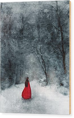Woman In Red Cape Walking In Snowy Woods Wood Print by Jill Battaglia